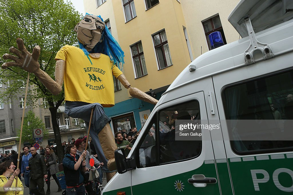 """Activists lead a giant puppet wearing a t-shirt that reads: 'Refugees Welcome' toward a police van prior to the """"Revolutionaerer 1. Mai"""" (Revolutionary May 1st) demonstration on May Day on May 1, 2103 in Berlin, Germany. Seven thousand police are on hand this year in Berlin to oversee the march that in years past has been plagued by violent clashes between marchers and police."""