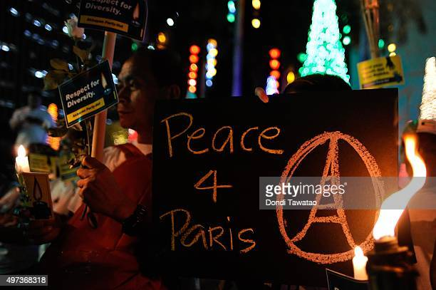 Activists light candles during a vigil held for the victims of the Paris terror attacks at the French Embassy on November 16 2015 in Manila...