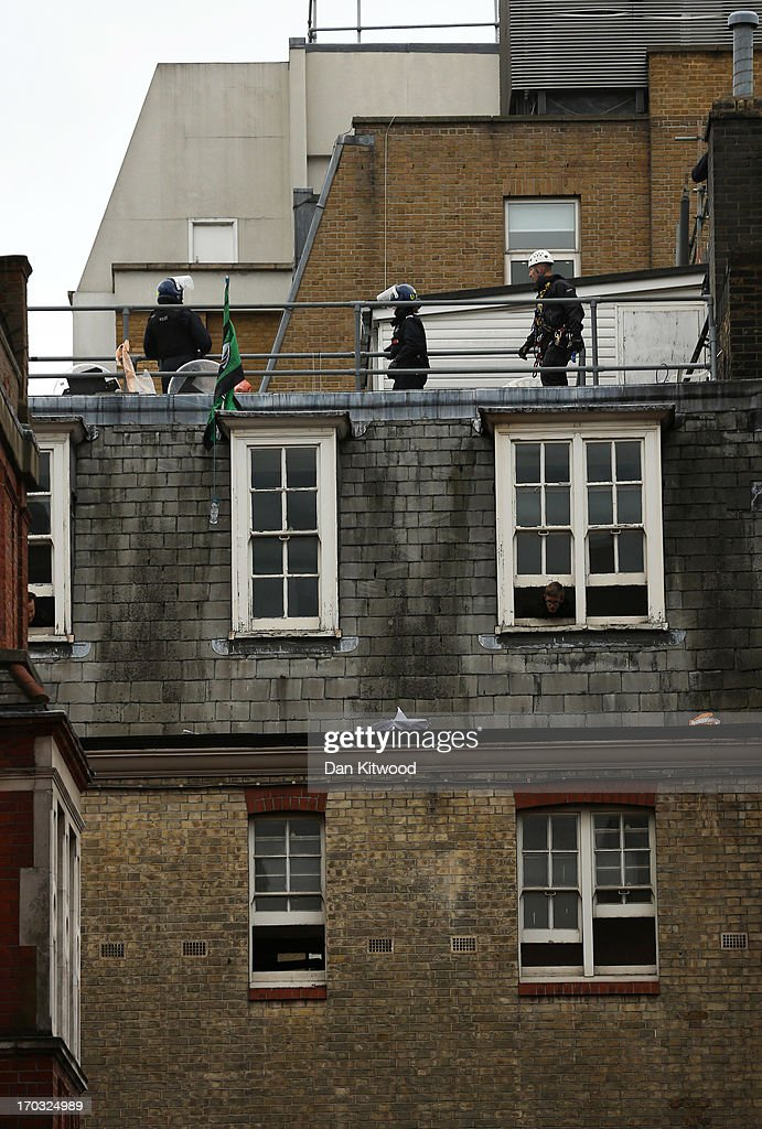 Activists look through windows as police stand guard on the rooftop of the convergence centre of the Stop G8 protest group off Beak Street ahead of next week's G8 summit in Northern Ireland on June 11, 2013 in London, England. Next week will see Enniskillen in Northern Ireland host the two day G8 summit where international leaders including Britain's Prime Minister David Cameron and US President Barack Obama take part in the two day event. The chosen location is only 8 kilometers from the scene of one of Northern Ireland's worst killings back in 1987, however Cameron is confident that it's secluded location will deter any potential trouble.