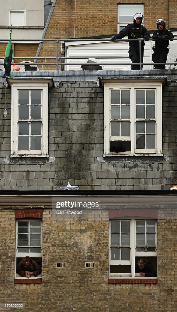 Activists look through windows as policeman stand guard on the rooftop of the convergence centre of the Stop G8 protest group off Beak Street ahead of next week's G8 summit in Northern Ireland on June 11, 2013 in London, England. Next week will see Enniskillen in Northern Ireland host the two day G8 summit where international leaders including Britain's Prime Minister David Cameron and US President Barack Obama take part in the two day event. The chosen location is only 8 kilometers from the scene of one of Northern Ireland's worst killings back in 1987, however Cameron is confident that it's secluded location will deter any potential trouble.