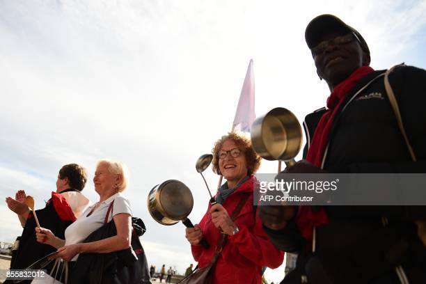 Activists make noise with kitchen utensils during a demonstration called for by La France Insoumise leftist party parliamentary group President...