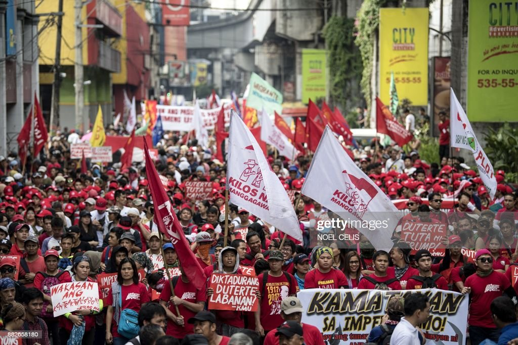 Activists march to the Malacanang palace during an anti-Duterte protest in Manila on November 30, 2017, denouncing the government's crackdown of activists and what they call US-backed Duterte dictartorship. Thousands of supporters and critics of Philippine President Rodrigo Duterte staged rallies on November 30 for and against his threat to declare a 'revolutionary government', which has fuelled fears of a looming dictatorship. /