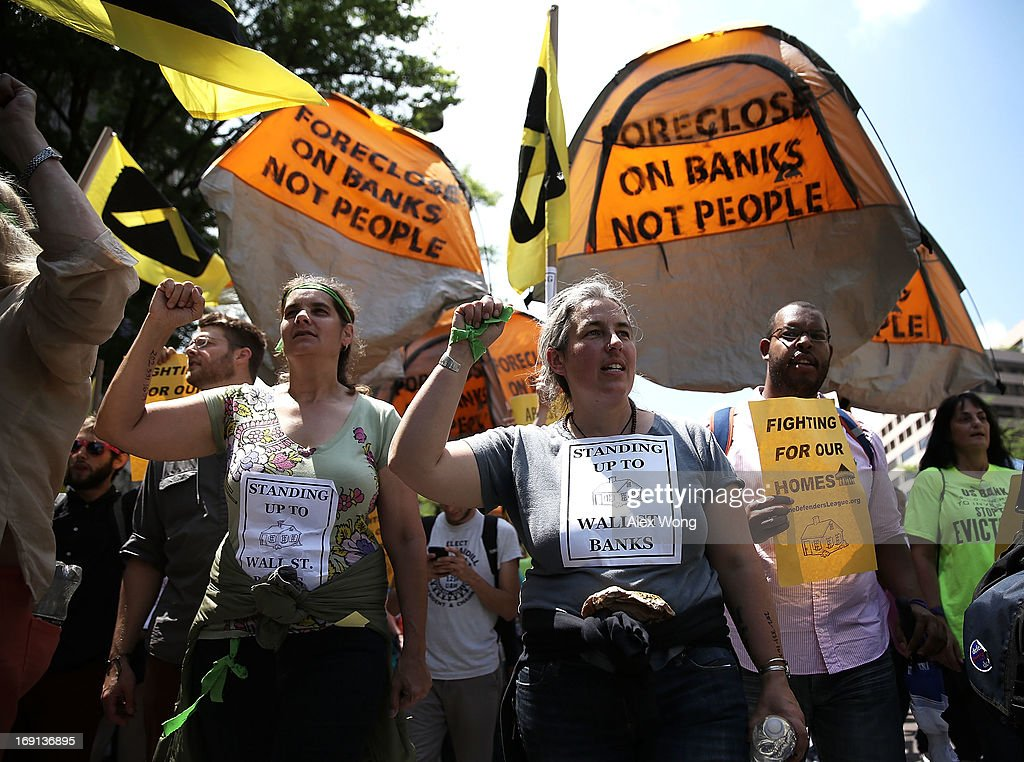 Activists march to the U.S. Justice Department as they participate in a protest May 20, 2013 in Washington, DC. Homeowners and activists from Home Defenders League and Occupy Homes joined the protest to demand that Attorney General Eric Holder 'hold Wall Street Banks that ravaged America's economy accountable.'