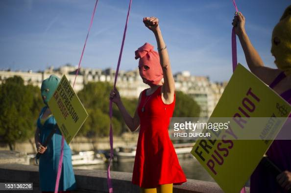 Activists of Amnesty International a nongovernmental organisation focused on human rights pose in front of the Eiffel tower on October 1 2012 in...