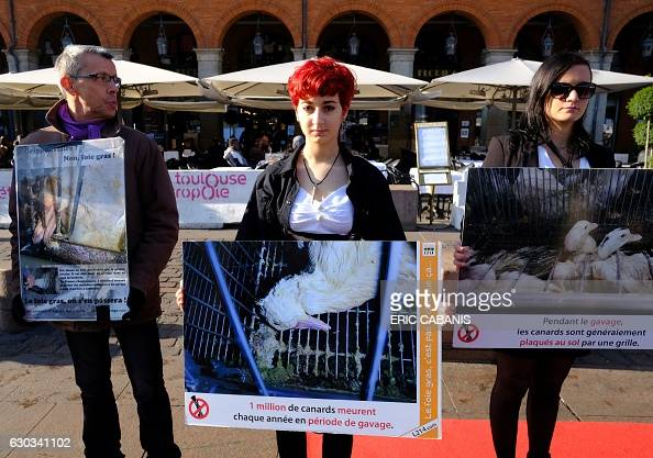 Activists of animal rights association L214 hold banners bearing pictures of ducks during a gathering to ask for the suppression of the forcefeeding...