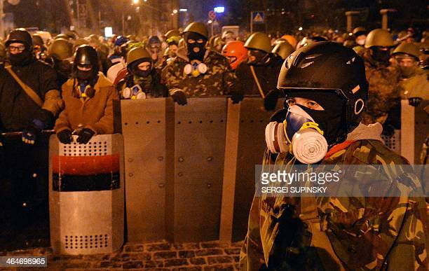 Activists of Euromaidan stand guard as other protesters build a new barricade in the center of the Kiev on the night of January 24 2014 Crunch talks...