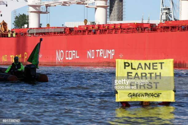 Activists of Greenpeace have painted 'No Coal No Trump' on the side of the 'SBI Subaru' ship with some 60000 tons of coal from Texas on board in...