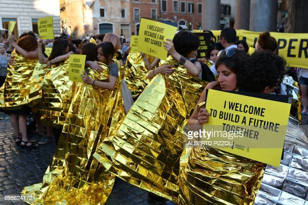 Activists of human rights organization Amnesty International hug in front of the Pantheon during a flashmob on World Refugee Day in central Rome on...