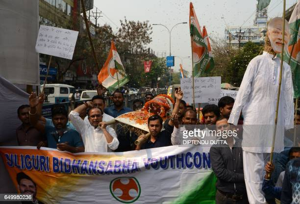 Activists of India's Youth Congress Party carry a empty Liquid Petroleum Gas cylinder as they shout slogans and wave placards during a rally in...