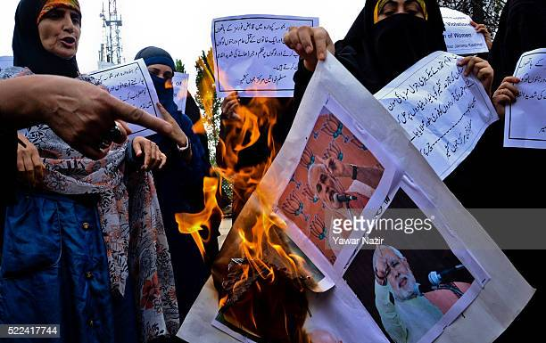 Activists of Muslim Khawateen Markaz a pro Kashmir women's resistance organization set pictures of Indian Prime Minister Narendra Damodardas Modi on...