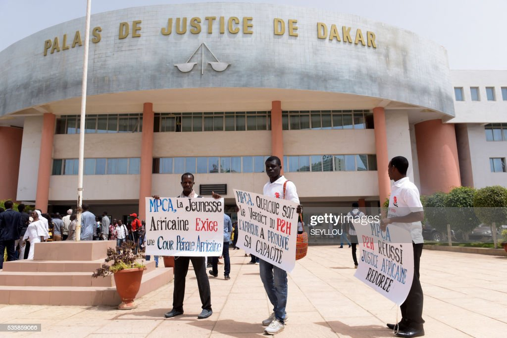 Activists of Peace Mobilisation and African Justice Consolidation association (Mobilisation pour la paix et la consolidation de la justice africaine) hold placards reading 'Africa's youth asks for a African Criminal Court' outside Dakar Courthouse ahead of the sentencing of former Chadian dictator Hissene Habre on May 30, 2016 in Dakar. Former Chadian dictator Hissene Habre was found guilty of crimes against humanity and sentenced to life in prison by a special court in Senegal on May 30, 2016. The case, at the Extraordinary African Chambers (CAE) - a special tribunal set up by the African Union under a deal with Senegal - is the first time a country has prosecuted a former leader of another nation for rights abuses. / AFP / SEYLLOU