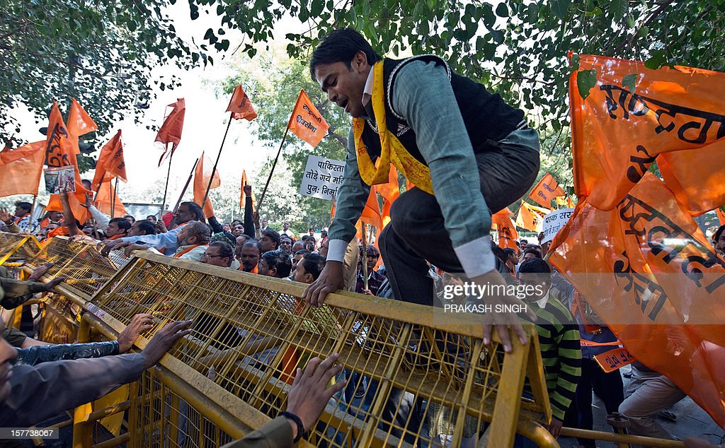 Activists of right wing Hindu Bajranj Dal and Rashtrwadi Sena activists climb on police barricade shout slogans against a Hindu temple demolition in Pakistan and demanding the construction of Ram Templein Ayodhaya during a protest to mark the demolition of the 16th century Babri Mosque, in Ayodhya on its 20th anniversary , in New Delhi on December 6,2012. The Babri mosque in the state of Uttar Pradesh was demolished by Hindu fundamentalists in 1992, claiming it was built on the site of the birth place of the Hindu God, Lord Rama. AFP PHOTO/ Prakash SINGH