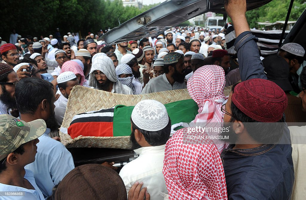 Activists of Sipah-e-Sahaba Pakistan move the coffin into a vechile during the funeral of a protestor who was killed during violent protests against a US-made anti-Islam film, in Karachi on September 22, 2012. Thousands of Islamist activists in Pakistan staged new demonstrations Saturday against a US-made anti-Islam film, as the death toll from the previous day's violent protests rose to 21. AFP PHOTO/Rizwan TABASSUM