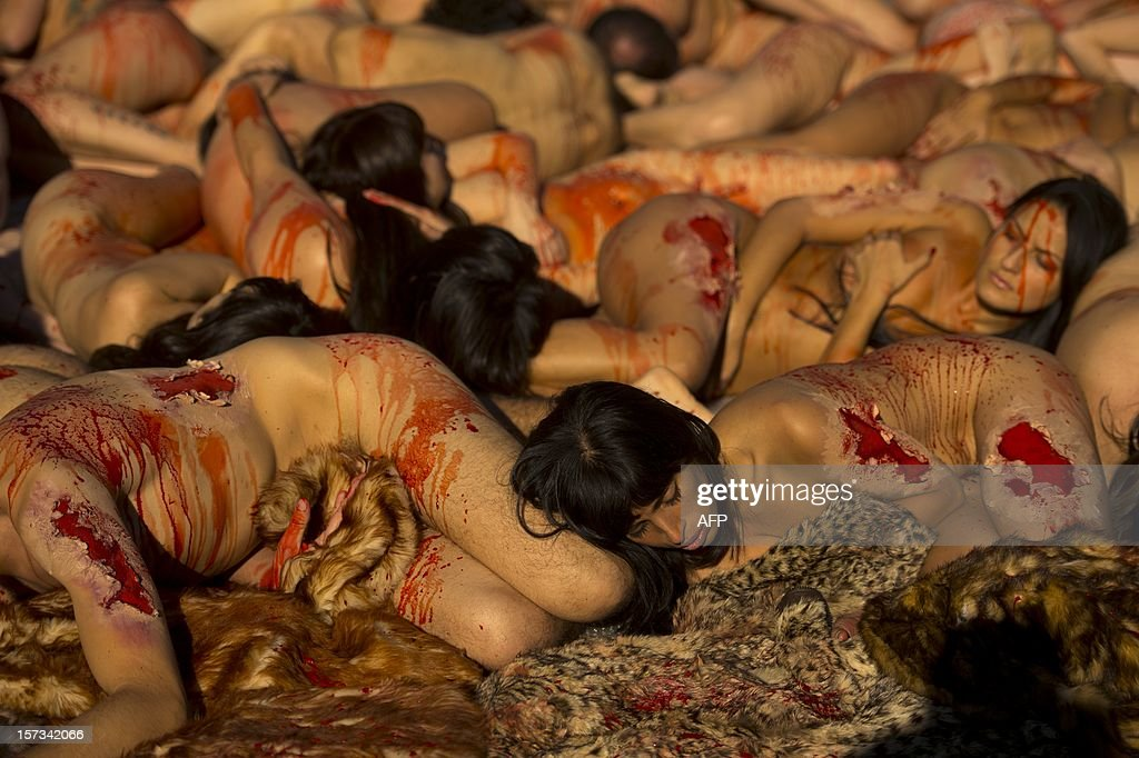 Activists of the animal-rights group AnimaNaturalis protest naked covered with fake blood against the use of fur in the textil industry in Madrid on December 2, 2012.
