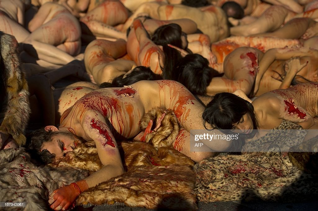 Activists of the animal-rights group AnimaNaturalis protest naked covered with fake blood against the use of fur in the textil industry in Madrid on December 2, 2012. AFP PHOTO/ PIERRE-PHILIPPE MARCOU