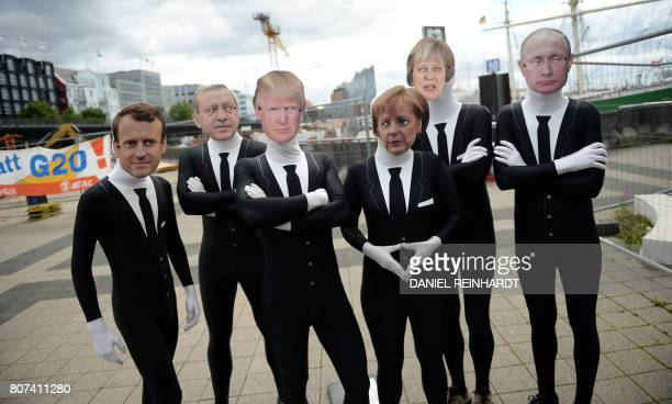 Activists of the 'Attac' network wear masks of French President Emmanuel Macron Turkish President Recep Tayyip Erdogan US President Donald Trump...