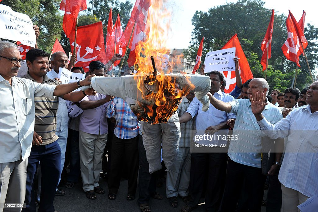 Activists of the Communist Party of India-Marxists(CPI-M) burn an effigy representing the United Progressive Alliance(UPA) during their protest against the rail fare hike, in Hyderabad on January 10, 2013. Union railways minister Pawan Kumar Bansal announced the fare hike to maintain safety and cleanliness with passenger fares hiked up from January 21. AFP PHOTO/Noah SEELAM