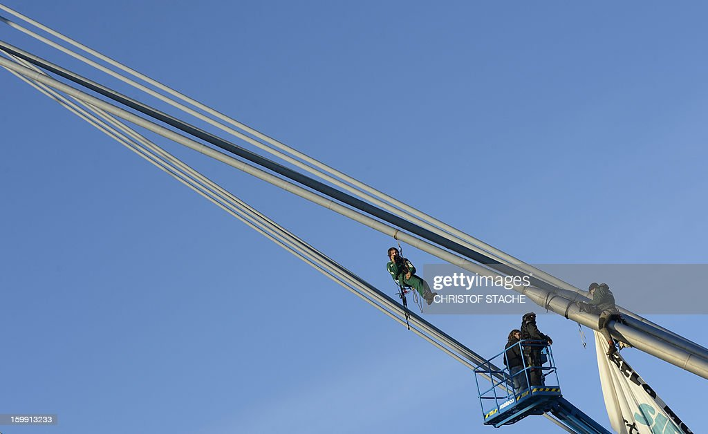 Activists of the environmental group 'Robin Wood' climb on a roof pole of the Olympic hall in Munich, southern Germany to raise a banner that reads 'Siemens dams: expulsion, greed, enviromental destruction' as the German industrial giant Siemens holds its annual shareholder meeting on January 23, 2013. Robin Wood protests against the participation of Siemens at an embankment dam project in Brazil.