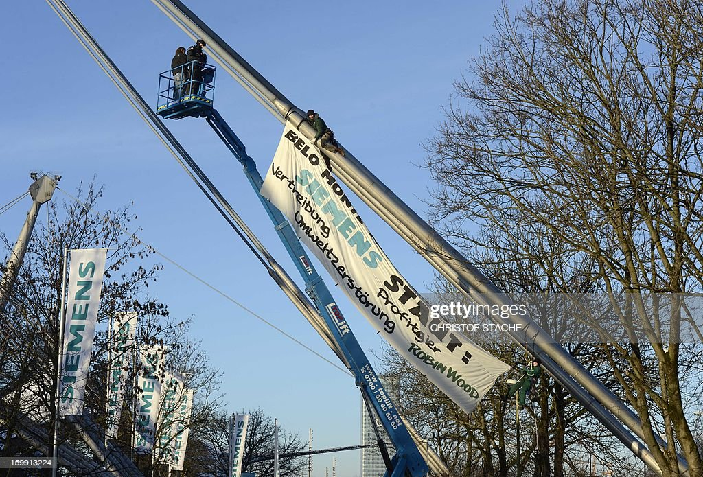 Activists of the environmental group 'Robin Wood' climb on the roof of the Olympic hall in Munich, southern Germany to raise a banner that reads 'Siemens dams: expulsion, greed, enviromental destruction' as the German industrial giant Siemens holds its annual shareholder meeting on January 23, 2013. Robin Wood protests against the participation of Siemens at an embankment dam project in Brazil. AFP PHOTO / CHRISTOF STACHE