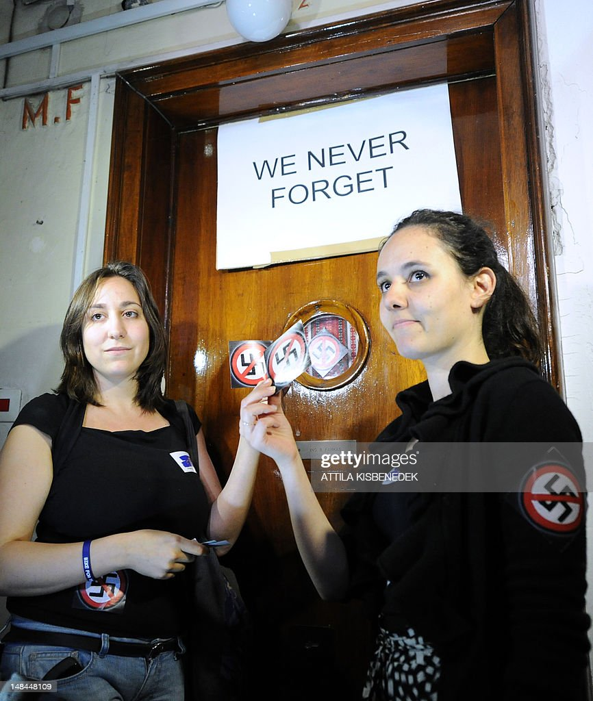 Activists of the European Union of Jewish Students organization hold up 'No Nazi' symbols in front of the door of Laszlo Csatary's hideaway building, only few kilometers from his home in Budapest on July 16, 2012 prior to their protest against Csatary, called after a Hungarian prosecutor said that investigating an aged Nazi war criminal found alive and well in Budapest was problematic because the events took place so long ago and in a different country. A probe into Laszlo Csatary, 97, began in September after information was received from the Nazi-hunting Simon Wiesenthal Center, which ranks him number one on their wanted list, the public prosecutors' office said.