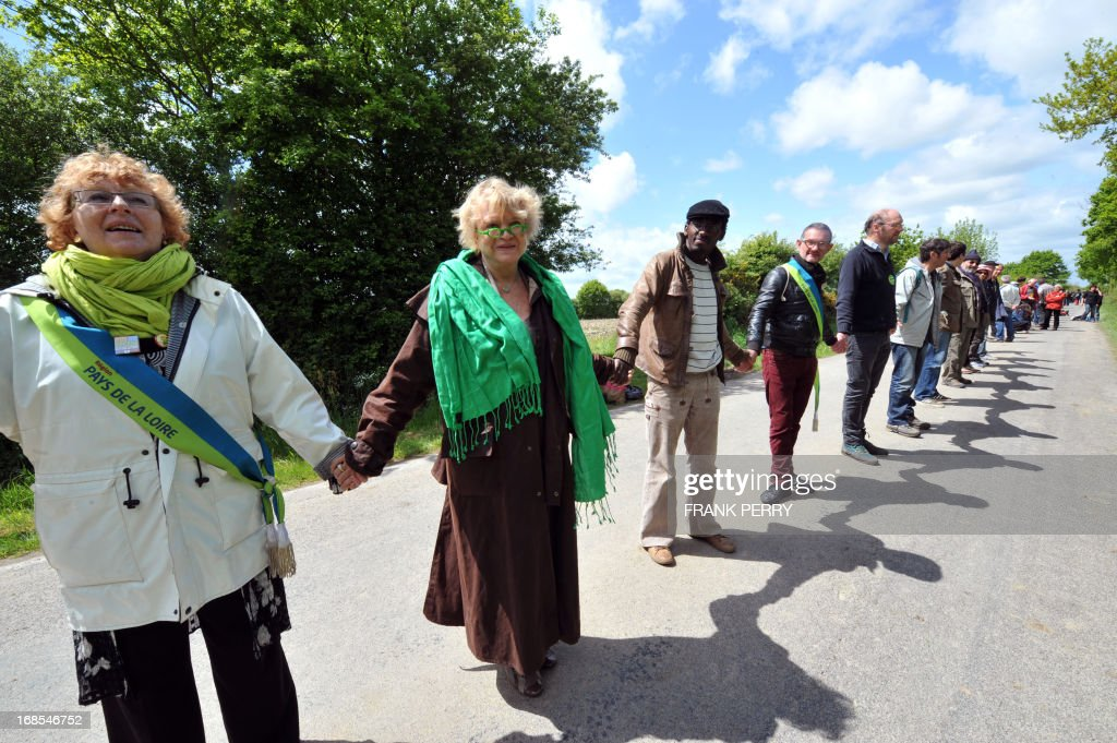 Activists of the French Green party, including European parliamentarian and former Green party presidential candidate Eva Joly (2nd L), hold hands and form a human chain as they take part in a protest against the construction of a new airport in Notre-Dame des Landes, on May 11, 2013. Several thousand protesters, at least 5 000 according to the local police department, gathered