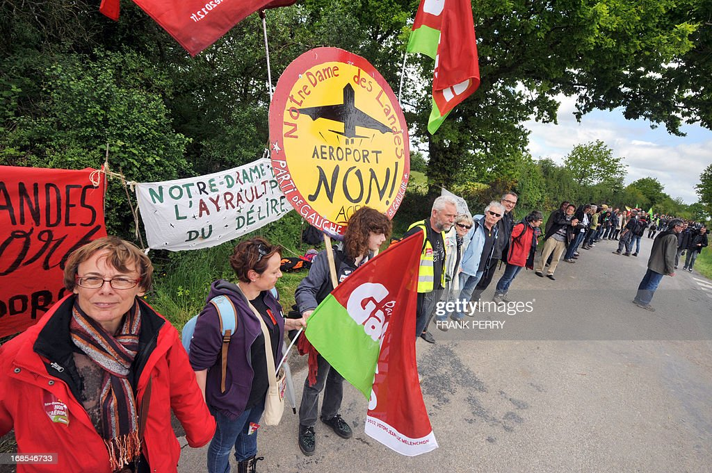 Activists of the French left-wing 'Front de Gauche' party, including the party's vice-President Martine Billard (L), hold hands and form a human chain as they take part in a protest against the construction of a new airport in Notre-Dame des Landes, on May 11, 2013. Several thousand protesters, at least 5 000 according to the local police department, gathered