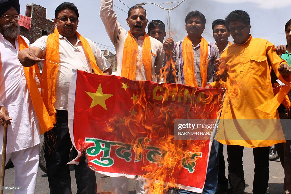 Activists of the Indian right-wing Hindu organisation Shiv Sena shout slogans as they burn a China national flag while protesting against the land grabbing by China in Ladakh during a demonstration in Amritsar on April 25, 2013. India's Foreign Minister Salman Khurshid said Thursday he would visit China on May 9 amid high tensions between the neighbours due to a flare-up at their disputed border. New Delhi says a platoon of Chinese troops moved into Indian territory on April 15 in a remote and desolate part of the Himalayas where the border is disputed.