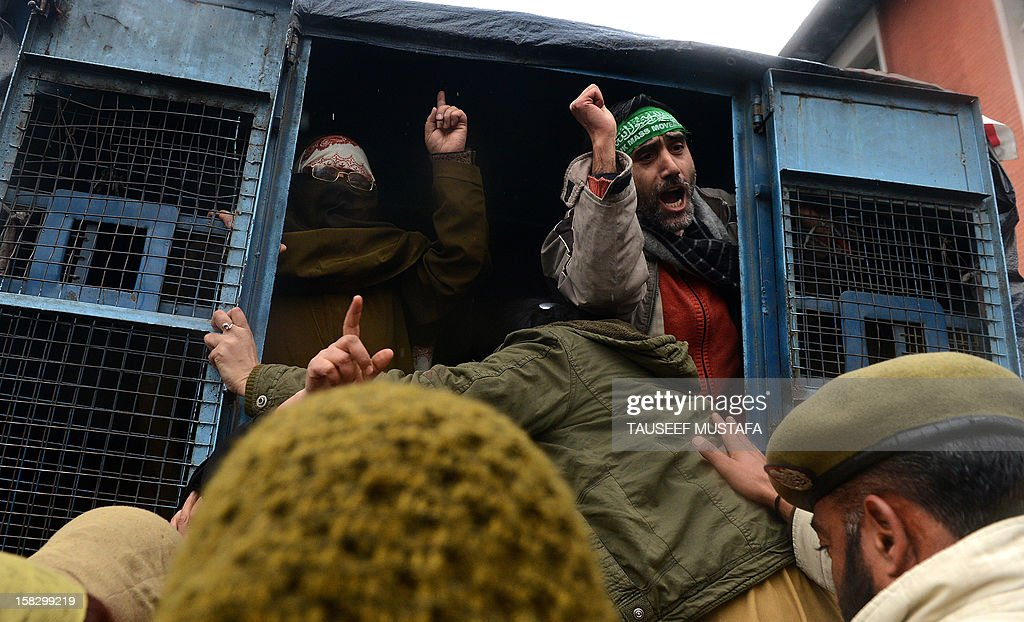 Activists of the Jammu and Kashmir Mass Movement (JKMM) shout anti-India slogans from a police van during a protest in support of clemency for Mohammad Afzal Guru in Srinagar on December 13, 2012. Indian police detained some half a dozen activists during the protest. Fellow Kashmiri, Mohammad Afzal Guru was sentenced to death by an Indian court after being found guilty of being involved in the 13 September 2001 attack on India's Parliament House in New Delhi. The protestors appealed to the President to commute the death sentence of Guru and reinvestigate the case. AFP PHOTO/Tauseef MUSTAFA
