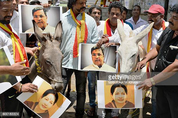 Activists of the Karnataka Rakshana Vedike hold posters of Karnataka Chief Minister Siddaramaiah and Tamil Nadu Chief Minister Jayalalithaa alongside...