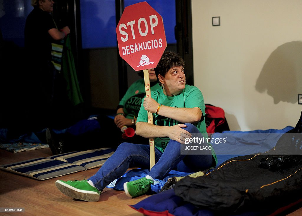 Activists of the PAH (the Platform of People Affected by Mortgage) occupy a block of flats owned by SAREB to protest against the evictions of people living in the building, in Salt, near Girona, on October 15, 2013. Forty-three people will be evicted of the building 'Bloc Salt' owned by bad bank Sareb on October 16. Spain set up Sareb, a 'bad bank', to buy bad assets from lenders and sell them for a profit after the euro zone agreed to finance a rescue of Spain's banks, swamped in bad loans since a property bubble imploded in 2008 plunging the country into a double-dip recession.