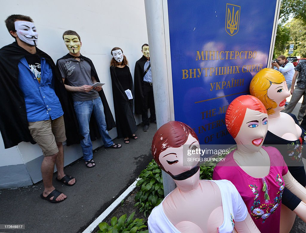Activists of the public initiative 'The movement of Guy Fawkes' stand back after placing inflatable dolls for adults in front of the Ukrainian Interior Ministry in Kiev during a protest-performance against the police outrage on July 4, 2013. Activists conducted a rally to support the residents of the small Ukrainian ciry of Vradiyivka, in Mykolayiv region, who stormed the local police headquarters after two police officers brutally beat and raped 29-year-old Iryna Krashkova. The huge outrage prompted Ukraine's President Viktor Yanukovych to order a top-level enquiry into the gang rape of Krashkova.
