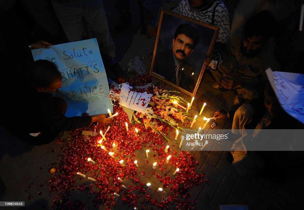 Activists of the ruling Pakistan Peoples party light candels in front of the picture of slain minority affairs minister Shahbaz Bhatti in Lahore on March 5, 2011. Bhatti, 42, an outspoken campaigner against Pakistan's Islamic blasphemy laws, died in a hail of bullets as he left his mother's home in the capital Islamabad. AFP PHOTO/Arif ALI