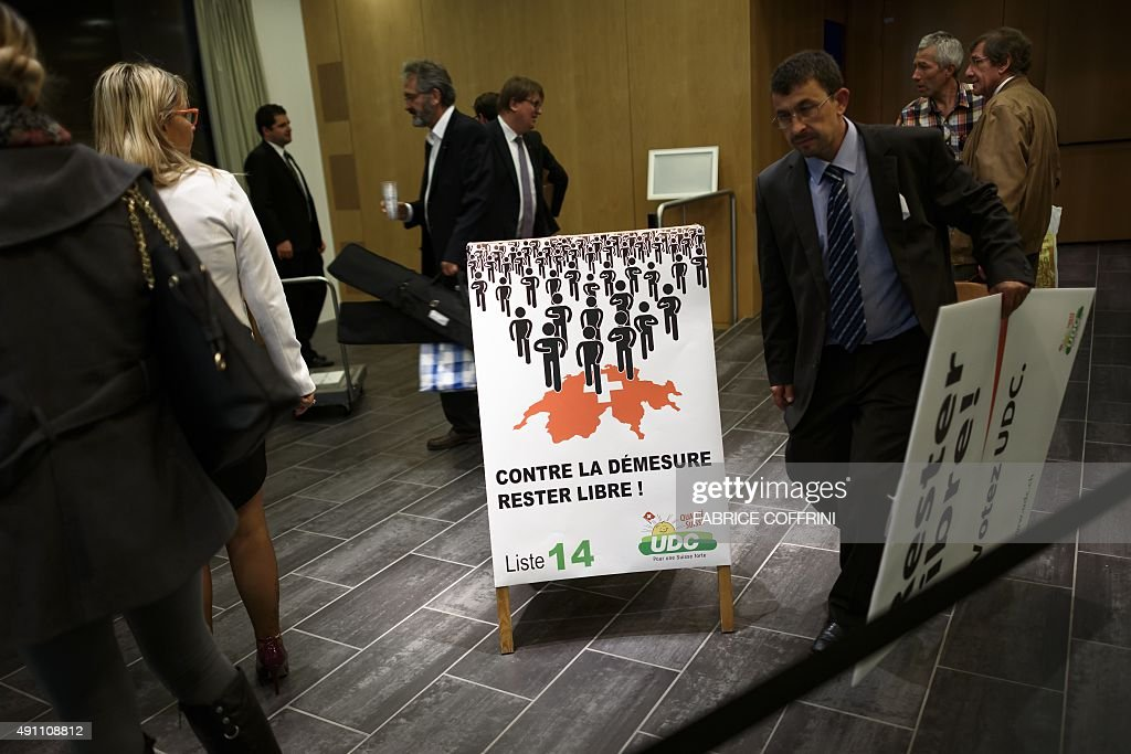 Activists of the Swiss Peoples Party popular for its immigration restriction proposals are seen after a meeting next to a electoral poster reading in...