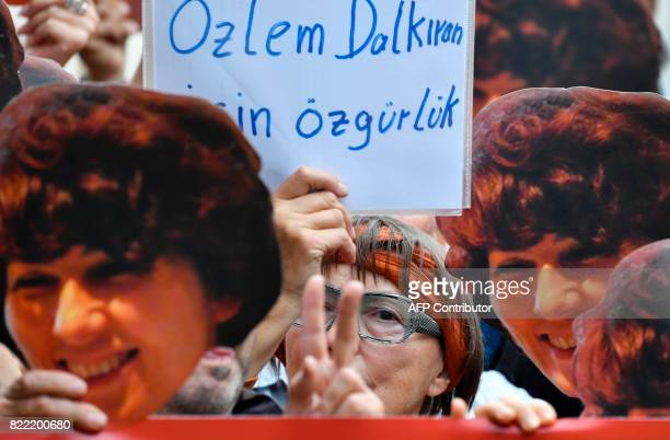 Activists of the USbased progressive NGO Avaaz wear masks featuring a photo of Turkish human rights activist Özlem Dalkiran during a demonstration in...