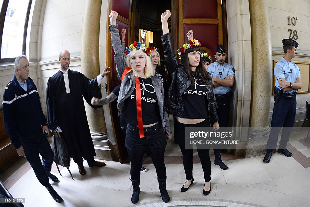 Activists of Ukrainian feminist protest group Femen raise their fists as they enter the courtroom prior to their hearing on charges of damaging Notre Dame cathedral during a demonstration earlier this year, on September 13, 2013 at Paris courthouse. On February 12, Femen activists, who had previously alerted news agencies, hid in the lines of tourists streaming into the historic cathedral before perching on the base of three new bells temporarily placed in the nave. AFP PHOTO LIONEL BONAVENTURE