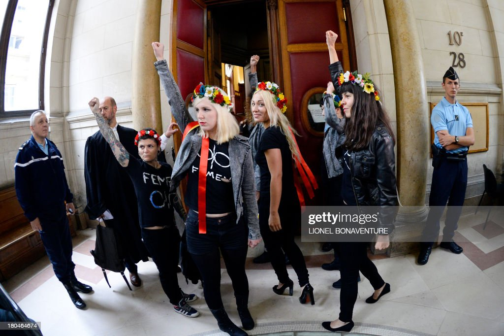 Activists of Ukrainian feminist protest group Femen raise their fists as they enter the courtroom prior to their hearing on charges of damaging Notre Dame cathedral during a demonstration earlier this year, on September 13, 2013 at Paris courthouse. On February 12, Femen activists, who had previously alerted news agencies, hid in the lines of tourists streaming into the historic cathedral before perching on the base of three new bells temporarily placed in the nave.