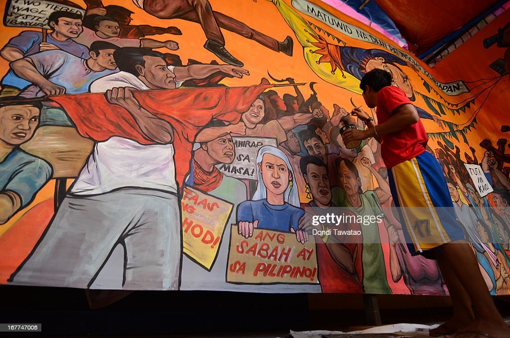 Activists paint a mural of Philippine president Benigno Aquino dressed as a clown being hounded by workers and peasants in preparation for the coming labor day protest rallies on April 29, 2013 in Quezon City, Philippines. Militant labor groups and trade unions are gearing up for protest rallies in front of the presidential palace on May 1 Labor Day citing the president's refusal to sign into law a wage increase which would benefit 8 million underemployed Filipinos. Despite the high poverty incidence remaining unchanged for the past six years The Philippines posted a healthy GDP growth, but government statistics show that the benefits of economic growth have yet to reach the poor.