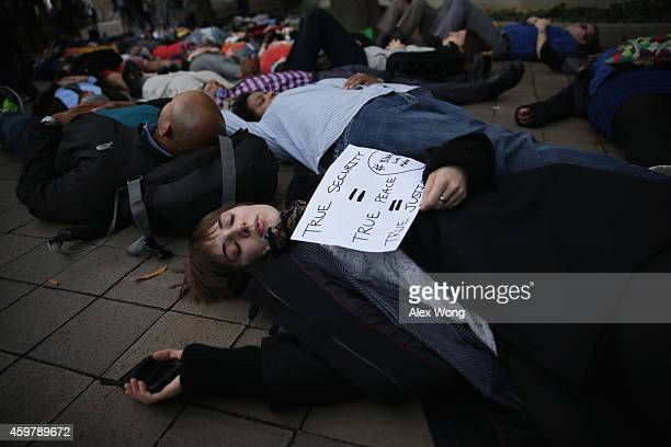Activists participate in a 'diein' by lying on the ground outside the Justice Department during a rally December 1 2014 in Washington DC Mass 'hands...