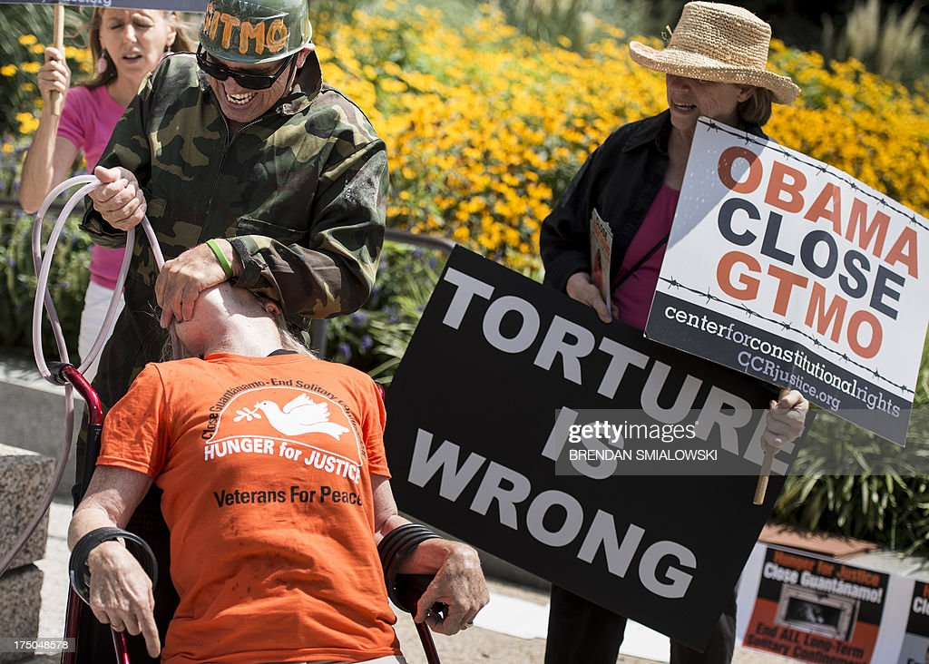 Activists participate in a mock force feeding while protesting outside the Hart Senate Office Building in Washington, DC July 30, 2013 . Activists gathered to protest the use of force feeding prisoners who are held in Guantanamo by the US government. President Barack Obama vowed to close the facility when he first took office in 2009, but four years on the military prison set up in the wake of the September 11, 2001 attacks still holds 166 men. The vast majority of those held at Guantanamo, detained on Afghan battlefields or handed over by other countries, have never been charged or tried, and dozens have been taking part in a hunger strike in recent months. Seventy detainees were taking part in the hunger strike as of July 23, with 46 of them listed as being fed through nasal tubes, according to the military. More than half of the detainees at Guantanamo have been cleared for release and face no charges in the United States. AFP PHOTO/Brendan SMIALOWSKI