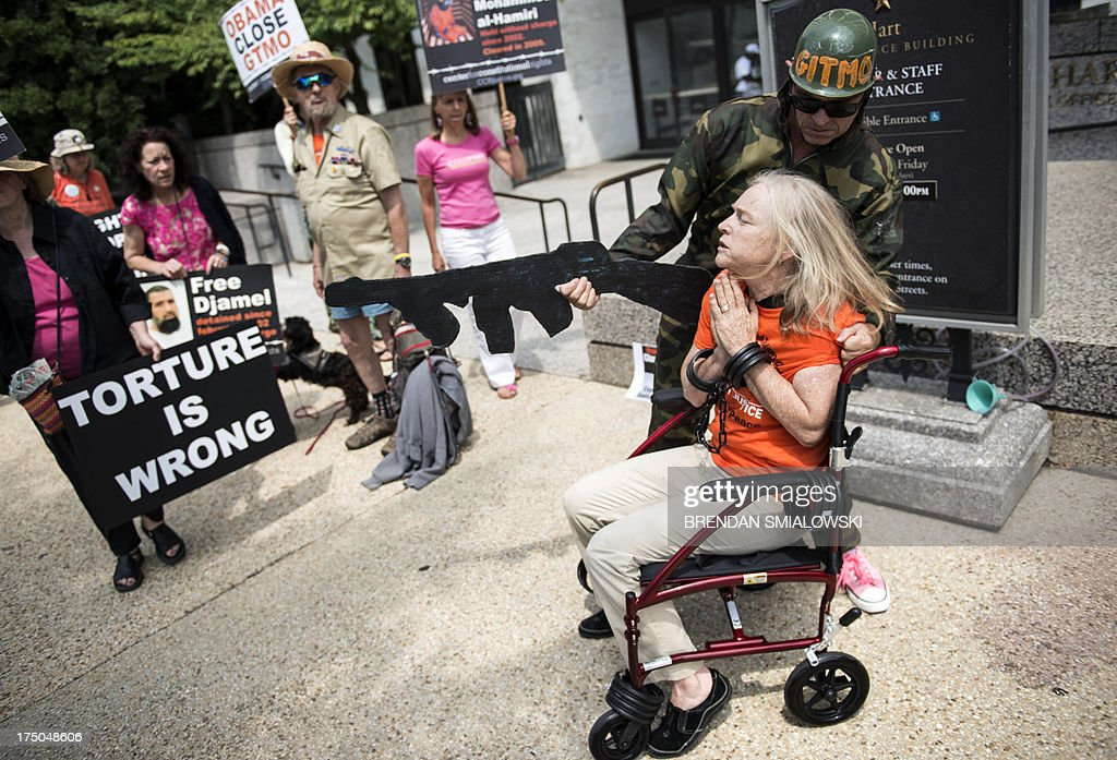Activists participate in a mock force feeding while protesting outside the Hart Senate Office Building July 30, 2013 in Washington, DC. Activists gathered to protest the use of force feeding prisoners who are held in Guantanamo by the US government. AFP PHOTO/Brendan SMIALOWSKI