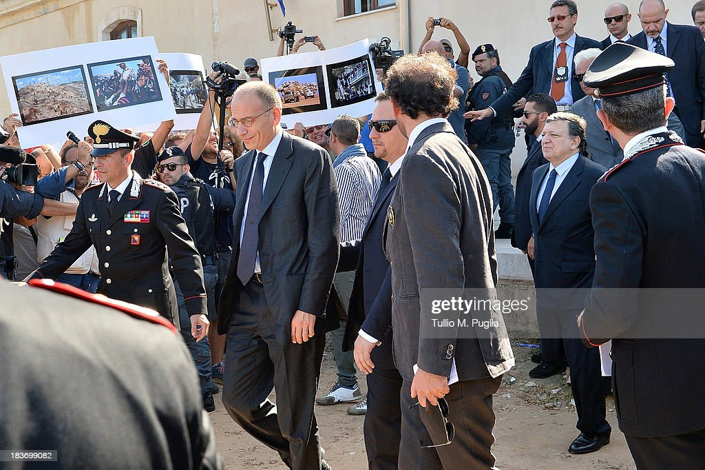 Activists protest as <a gi-track='captionPersonalityLinkClicked' href=/galleries/search?phrase=Enrico+Letta&family=editorial&specificpeople=2915592 ng-click='$event.stopPropagation()'>Enrico Letta</a>, Italian Prime Minister, (C) and Manuel Barroso, President of the European Commission (R) leave the Town Hall of Lampedusa on October 9, 2013 in Lampedusa, Italy. EU chief Barroso announced 30 million euros will be made available to help Italy settle refugees, during his visit to the island of Lampedusa today in the aftermath of the migrant boat sinking.