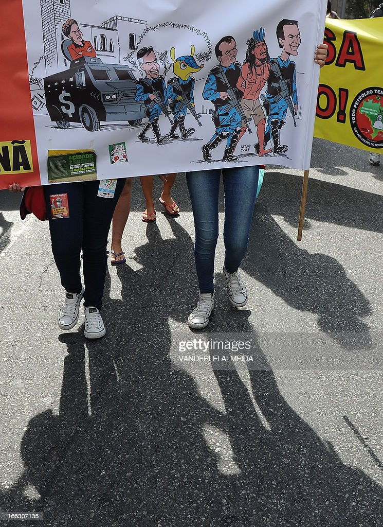 Activists protest in front of the Guanabara state government's palace against the privatization of the Mario Filho 'Maracana' stadium in Rio de Janeiro, Brazil, on April 11, 2013. Bidding for the privatization of Rio's iconic Maracana stadium was to go ahead as planned Thursday after a local court rejected an appeal to block the process. Maracana, which was built for the 1950 World Cup, is undergoing extensive renovation at a cost of 430 million dollars to host four Confederations Cup matches in June as well as seven World Cup games next year, including the finals of both tournaments. AFP PHOTO /VANDERLEI ALMEIDA