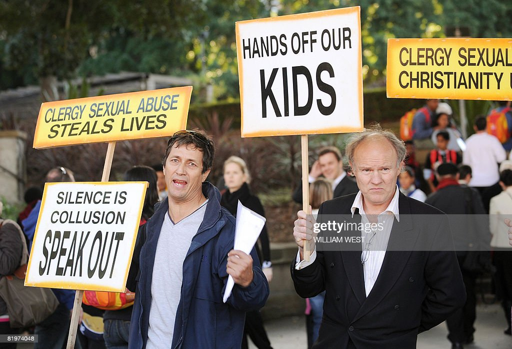 Activists protesting sexual abuse in the Catholic church hold up placards outside St Mary's Cathedral as Pope Benedict XVI watches the 'Stations of...