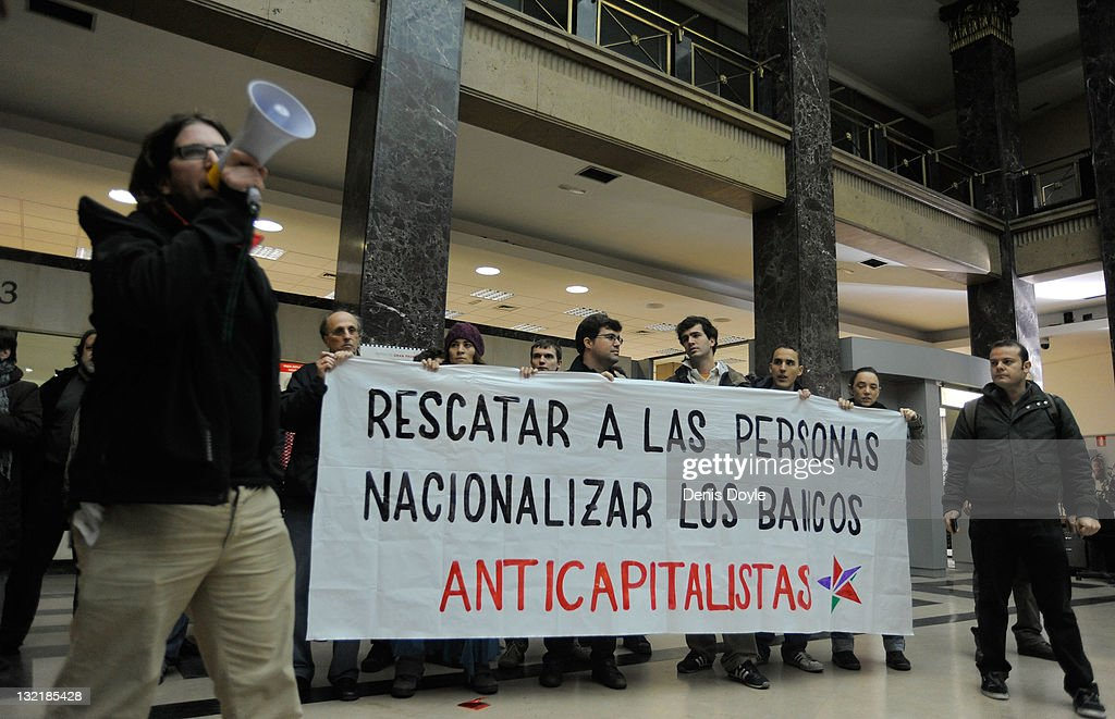 Activists protrest inside a branch of Banco Santander with a banner which reads 'Rescue people, nationalise banks' on November 8, 2011 in Madrid, Spain. The current Eurozone debt crisis has left Spain with crippling economic problems. Mounting debts, record unemployment figures and the recent credit rating downgrade is leaving the country facing further economic stagnation. The people of Spain are preparing to go to the polls for a general election which will be held on November 20, 2011.