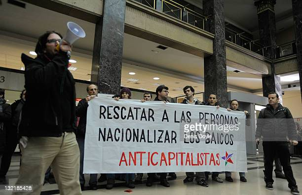 Activists protrest inside a branch of Banco Santander with a banner which reads 'Rescue people nationalise banks' on November 8 2011 in Madrid Spain...