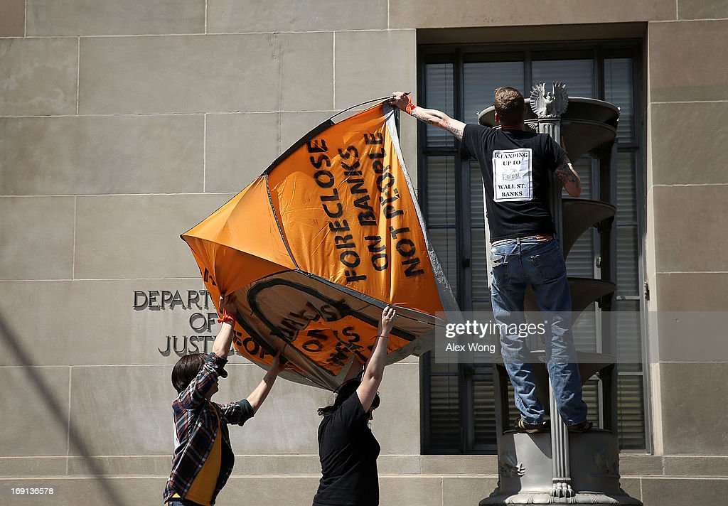 Activists put up a tent as they participate in civil disobedience during a protest outside the U.S. Justice Department May 20, 2013 in Washington, DC. Homeowners and activists from Home Defenders League and Occupy Homes joined the protest to demand that Attorney General Eric Holder 'hold Wall Street Banks that ravaged America's economy accountable.'