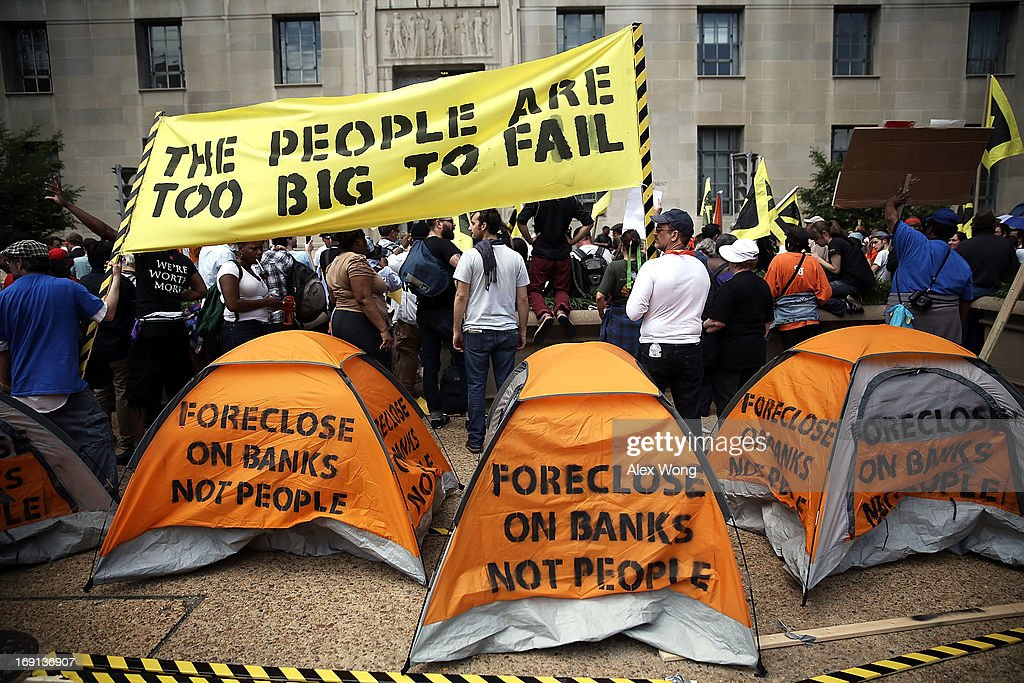Activists put up tents as they participate in civil disobedience during a protest outside the U.S. Justice Department May 20, 2013 in Washington, DC. Homeowners and activists from Home Defenders League and Occupy Homes joined the protest to demand that Attorney General Eric Holder 'hold Wall Street Banks that ravaged America's economy accountable.'
