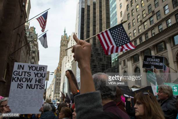 Activists raise their middle fingers as they pass near Trump Tower during a Tax Day protest on April 15 2017 in New York City Thousands of activists...