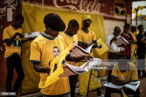 Activists read material as they gather ahead of the address of the leader of the Angolan opposition party CASACE Abel Chivukuvuku at an electoral...