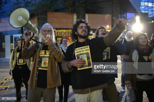 Activists shout slogans and wave posters as they stage a demonstration against the use of pesticides such as Glyphosate in agriculture outside The...